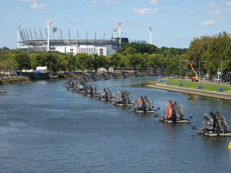 Water creatures representing nations of the Commonwealth are anchored to pontoons along the Yarra River with the MCG (Commonwealth Games stadium) in the background